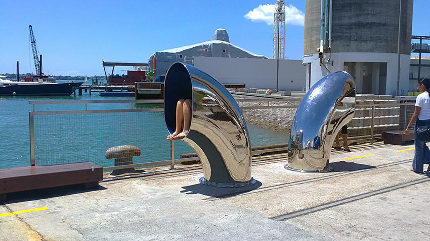 Two stainless steel ship's ventilators at the edge of North Wharf, Auckland; bare legs are visible on inside the funnel of the one on the right; dangling legs the one on the left
