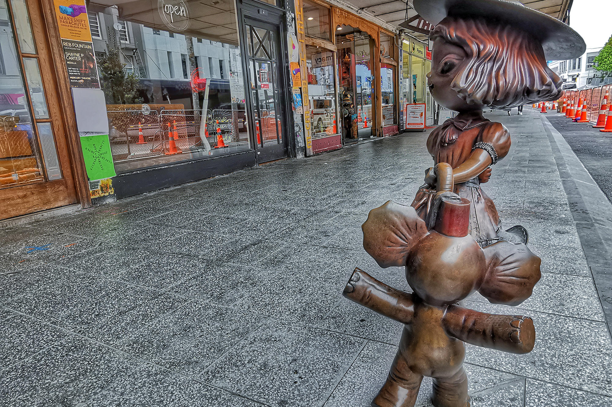 Bronze figurine of a girl in vintage clothes and hat dancing with a baby elephant set in streetscape