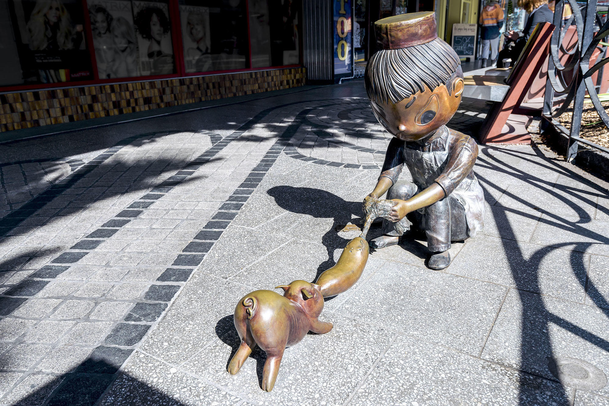 Bronze figurines set in streetscape of a boy in an apron wrestling a turnip from a piglet's mouth